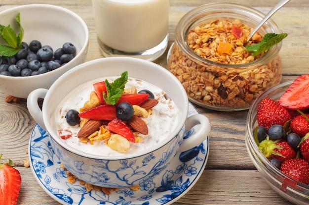 Bol de granola fait maison avec du yaourt et des baies fraîches sur fond en bois