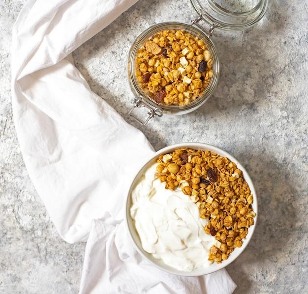 Bol de granola maison avec du yaourt grec sur un fond clair. vue de dessus