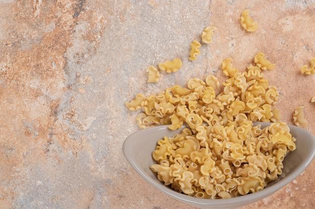 Un bol gris de macaronis non préparés sur un espace en marbre.