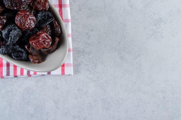Bol gris de savoureuses dattes séchées sur nappe rayée.