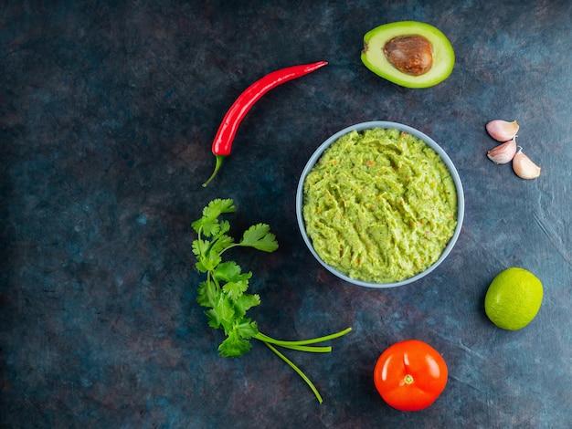 Bol de guacamole avec des ingrédients. sauce guacamole et piment, citron vert, avocat, persil, ail, tomate sur fond sombre. nourriture mexicaine. espace de copie. vue de dessus