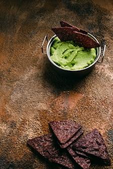 Bol guacamole et nachos sur fond de bois. vue de dessus