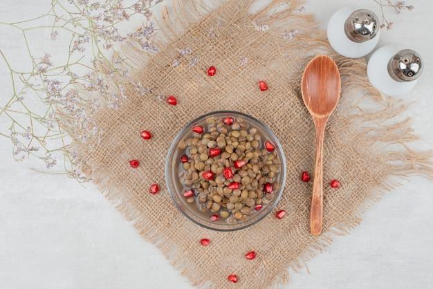 Bol de haricots bouillis avec des graines de grenade et du sel sur la toile de jute.