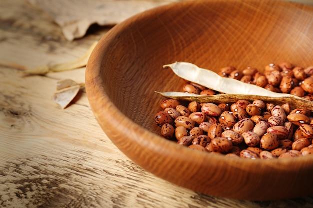 Bol avec haricots bruns sur table en bois