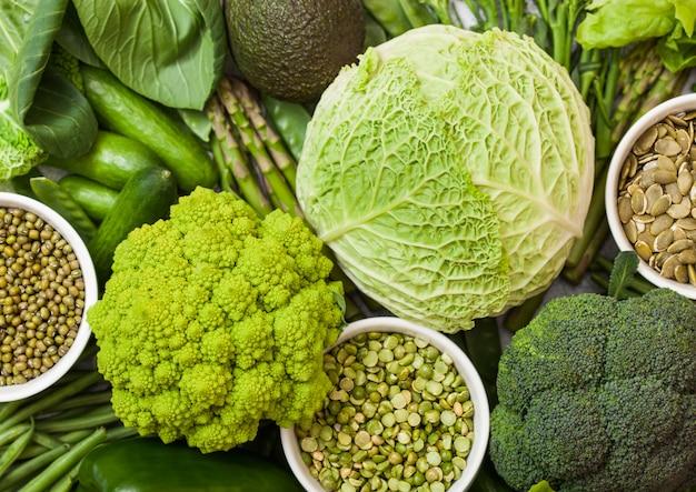Bol de haricots mungo et pois cassés et graines de citrouille avec des légumes crus biologiques aux tons verts. macro