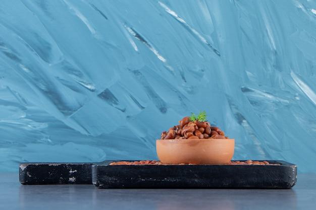 Bol de haricots sur le plateau de haricots, sur le fond bleu.