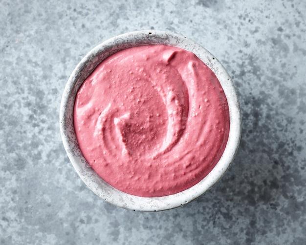 Bol de houmous de betterave rose sur une table de cuisine grise, vue de dessus