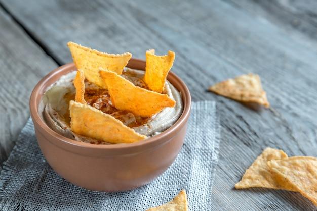 Un bol d'houmous avec des chips de maïs