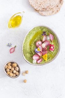 Bol d'houmous vert avec radis cuit au four et fleurs comestibles