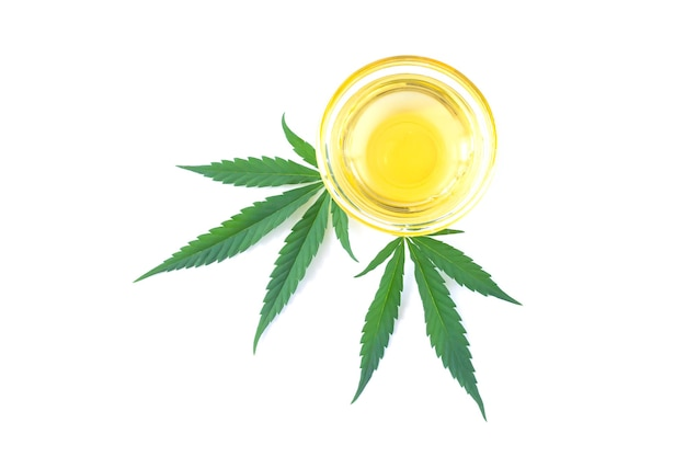 Bol d'huile de chanvre et feuille de cannabis isolé sur fond blanc
