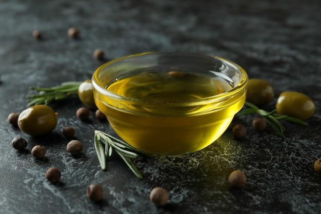 Bol d'huile d'olive, olives, poivre et romarin sur fond noir fumé