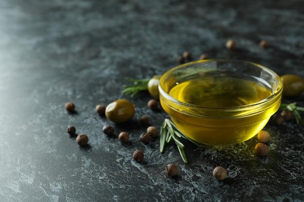Bol d'huile d'olive, olives, poivre et romarin sur fumée noire