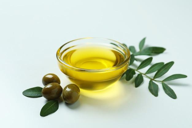 Bol d'huile, olives et brindilles sur blanc