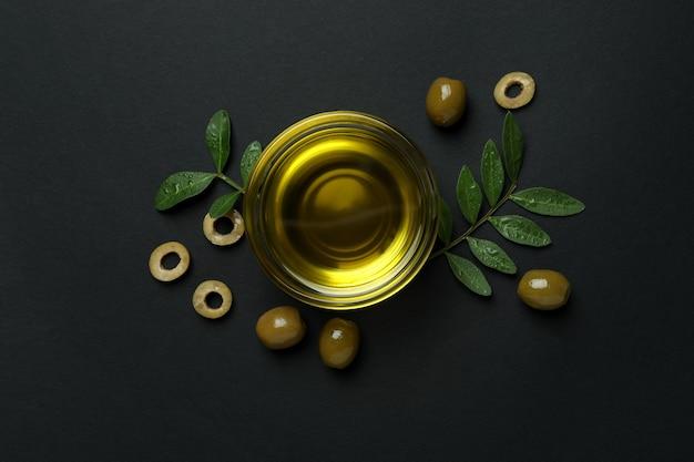 Bol d'huile, olives et brindilles sur fond noir
