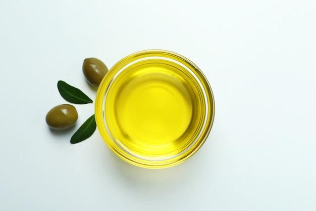 Bol d'huile, d'olives et de feuilles sur blanc
