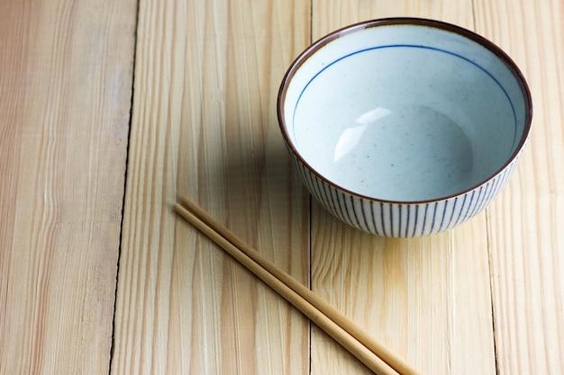 Bol japonais et baguettes sur la table en bois.
