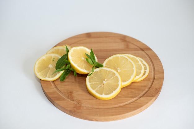 Bol de jus de citron fraîchement pressé, presse-citron et citrons mûrs sur une planche à découper en bois