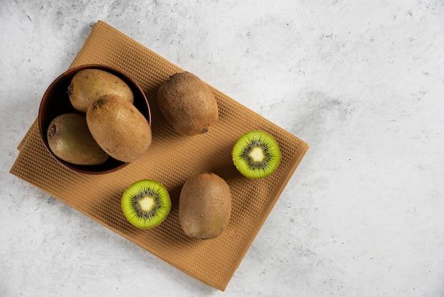 Bol avec des kiwis frais sur nappe marron