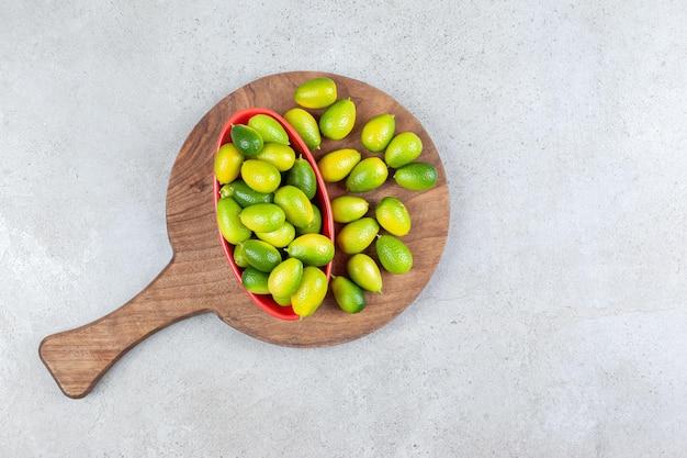 Bol de kumquats à côté d'un tas sur une planche en bois sur fond de marbre.