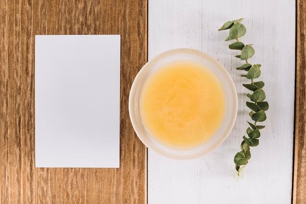 Bol de lait caillé au citron; feuilles et papier blanc vierge sur la double toile de fond en bois