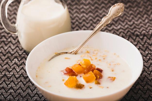 Bol à lait avec des garnitures de fruits sur la nappe
