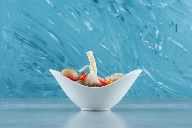 Un bol de légumes fermentés mixtes sur la surface bleue