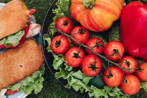 Bol de légumes frais à côté des sandwichs.