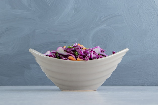 Un bol de légumes râpés, sur le marbre.