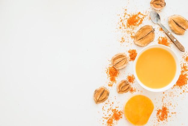 Bol avec un liquide orange entre le feuillage et le poivre
