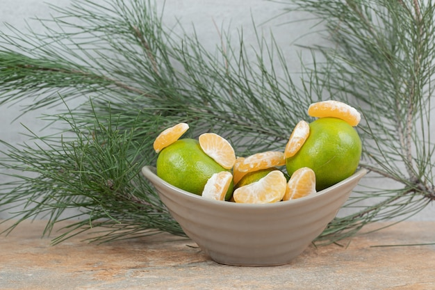 Bol de mandarine fraîche et segments sur table en marbre.