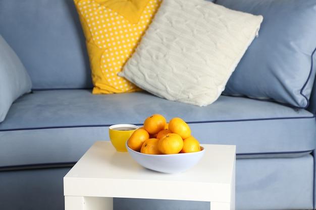 Bol avec des mandarines fraîches sur table dans le salon, gros plan