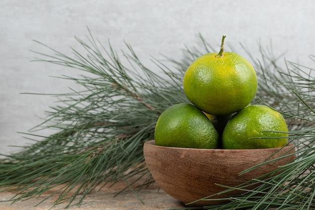 Bol de mandarines fraîches sur table en marbre avec branche.