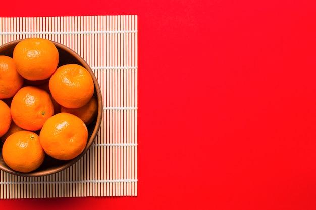 Bol avec des mandarines sur une serviette en bambou