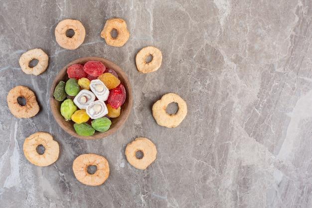 Bol de marmelades et lokums au milieu d'un anneau de tranche d'applie séchée sur marbre.