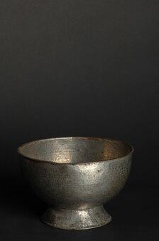 Bol en métal antique sur fond sombre. vaisselle en bronze antique