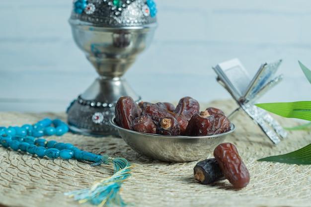 Bol en métal de délicieuses dates sur table en bois.