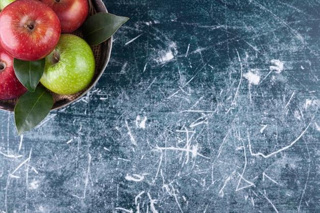Bol en métal avec pommes mûres rouges et vertes sur marbre.