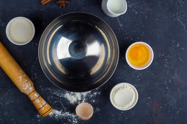 Bol en métal vide parmi les ingrédients et les ustensiles pour la cuisson du gâteau (farine, œuf, lait, sucre, rouleau à pâtisserie, serviette) sur une table sombre. concept alimentaire. vue de dessus, mise à plat, espace de copie pour le texte