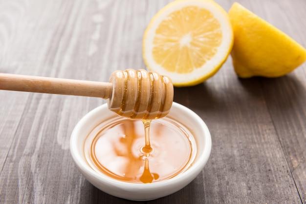 Bol de miel doux et citrons sur table en bois