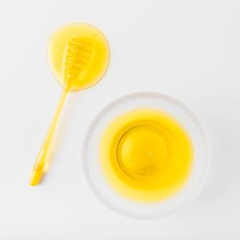 Bol de miel et louche sur une surface blanche