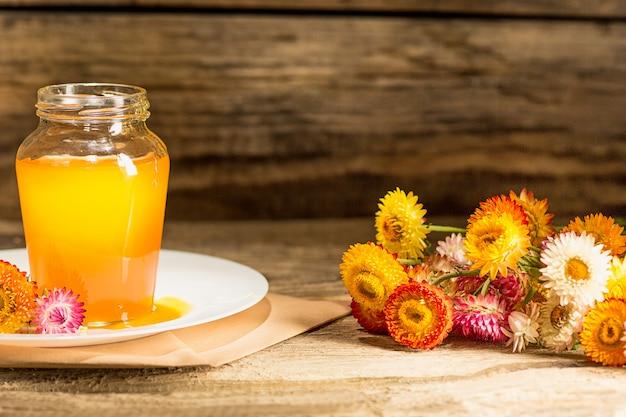 Le bol de miel sur une table en bois.la banque de miel reste près d'une cuillère en bois