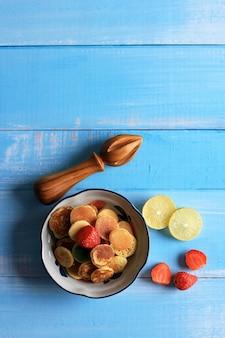 Bol avec de minuscules crêpes de céréales avec des fraises, du citron et des feuilles de menthe sur fond bleu. nourriture à la mode. mini crêpes aux céréales. orientation portrait avec espace de copie