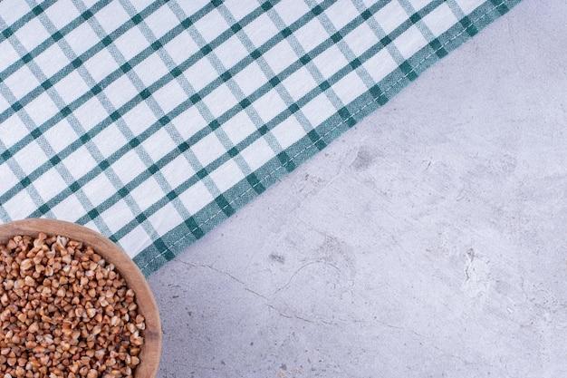 Bol modeste de sarrasin sur une serviette étalée sur fond de marbre. photo de haute qualité