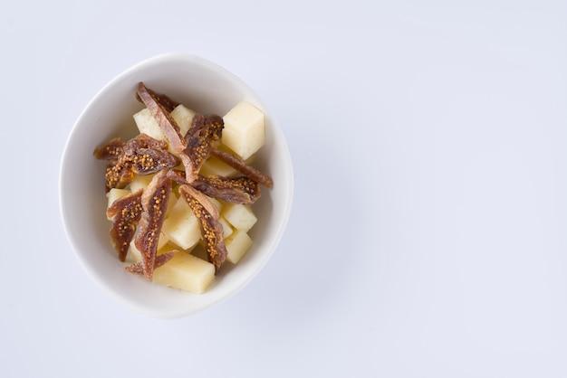 Bol de morceaux de savoureuse figue séchée et de morceaux de fromage pecorino sur fond blanc