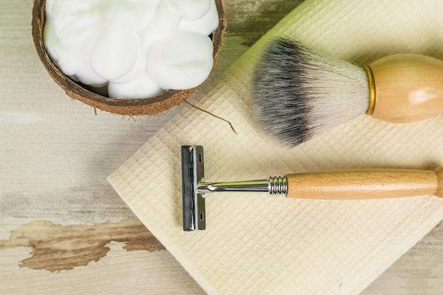 Un bol de mousse à raser, une brosse et un rasoir sur une serviette sur une table en bois. accessoires pour hommes pour le soin de l'apparence. mise à plat.