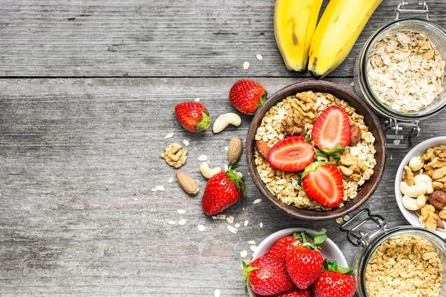 Bol de muesli à l'avoine avec fraise, granola, banane et noix