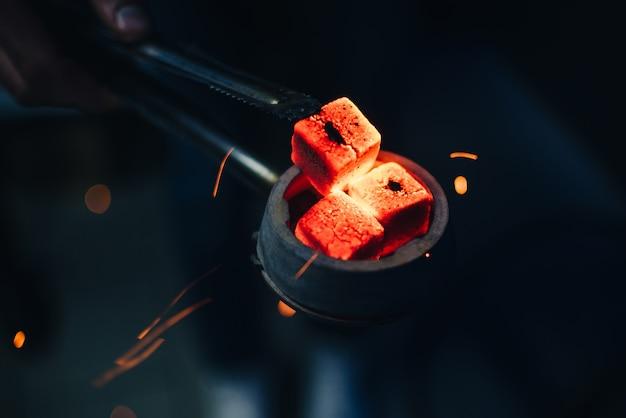 Bol de narguilé avec des charbons ardents rouges dans les mains de narguilé