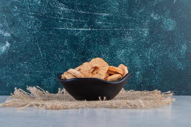 Bol noir d'anneaux de pommes séchées en bonne santé sur fond de pierre