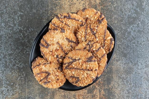 Un bol noir avec de délicieux biscuits croustillants