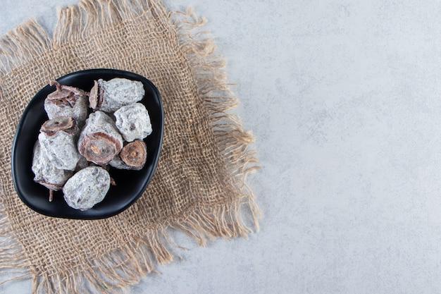 Bol noir de fruits kaki séchés sur fond de marbre.